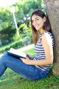 Happy young student reading book in a park of college Royalty Free Stock Photography
