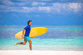 Happy young surf man runing at the beach with a strong surfboard Royalty Free Stock Images