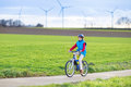 Happy young teenager boy riding his bike in a beautiful european landscape with energy wind mills Royalty Free Stock Photography