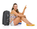 Happy young tourist woman sitting near wheel bag pointing copy space Stock Photography