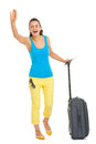 Happy young tourist woman with wheel bag saluting full length portrait of Stock Photo