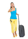 Happy young tourist woman with wheel bag showing thumbs up full length portrait of Stock Images