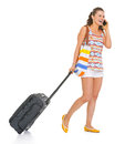 Happy young tourist woman wheel bag walking talking mobile phone Stock Photography