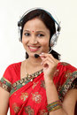 Happy young traditional woman wearing headset against white Royalty Free Stock Photo