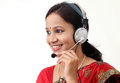 Happy young traditional woman wearing headset against white Royalty Free Stock Photography