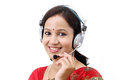 Happy young traditional woman wearing headset against white background Stock Photos