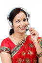 Happy young traditional woman wearing headset against white background Royalty Free Stock Photography