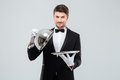 Happy young waiter lifting metal cloche from serving tray Royalty Free Stock Photo