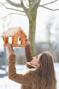 Happy young woman adding meal into bird feeder with long hair Royalty Free Stock Image
