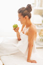 Happy young woman with apple sitting on massage table in spa salon Stock Images