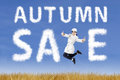 Happy young woman with autumn sale sign jumping Royalty Free Stock Photography