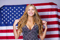 Happy young woman on a background of the American flag Royalty Free Stock Photo
