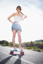 Happy young woman balancing on her skateboard a deserted road Stock Photos