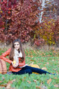 Happy young woman with basket of fresh apples sitting on meadow on bright autumn day Royalty Free Stock Image