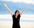 Happy young woman on beach arms outstretched biracial to the sky smiling Stock Photo
