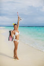 Happy young woman on the beach snorkeling walking enjoying sun and holidays travel in sunny sunshine wearing bikini holding Royalty Free Stock Images