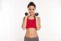 Happy young woman with a beautiful smile working out with dumbbells with both hands raised above her shoulders as she faces the Royalty Free Stock Photo