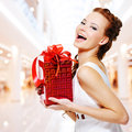 Happy young woman with birthday present in hands posing indoors Royalty Free Stock Photo
