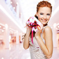 Happy young woman with birthday present in hands posing indoors Stock Images