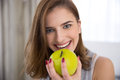 Happy young woman bitting green apple