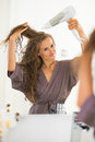 Happy young woman blow drying hair in bathroom Royalty Free Stock Photo