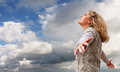 Happy young woman on the blue cloudy sky view Stock Photo