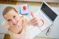 Happy young woman with books and laptop in kitchen showing thumbs up Royalty Free Stock Photos