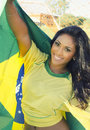 Happy young woman in brazil football top pretty beautiful wearing soccer holding brazilian national flag concept image for Stock Images
