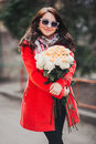 Happy young woman in bright coat with flowers goes through the city. Beautiful girl holding rose bouquet and smiling. A Royalty Free Stock Photo