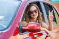 Happy young woman in car driving on the road. Royalty Free Stock Photo