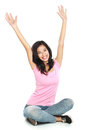Happy young woman in casual wear sitting with raised arms smilin Royalty Free Stock Photo