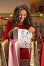 Happy young woman checking bags after christmas shopping in decorated kitchen Royalty Free Stock Images