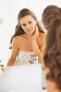 Happy young woman checking facial skin condition in bathroom with long hair hecking Stock Image