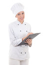 Happy young woman in chef uniform writing something in clipboard isolated on white background Royalty Free Stock Photography