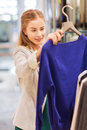 Happy young woman choosing clothes in mall sale consumerism shopping and people concept Stock Photos
