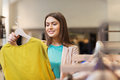 Happy young woman choosing clothes in mall sale shopping fashion style and people concept or clothing store Stock Photos