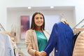 Happy young woman choosing clothes in mall sale shopping fashion style and people concept or clothing store Royalty Free Stock Photos