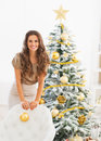 Happy young woman with christmas ball near christmas tree in living room Royalty Free Stock Photos