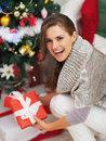 Happy young woman with christmas present box near christmas tree high resolution photo Royalty Free Stock Image