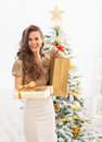 Happy young woman christmas present boxes in front of christmas Royalty Free Stock Photo