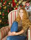 Happy young woman by the Christmas tree Royalty Free Stock Photo