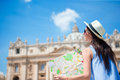 Happy young woman with city map in Vatican city and St. Peter's Basilica church, Rome, Italy. Travel tourist woman with Royalty Free Stock Photo