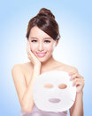 Happy young woman with cloth facial mask isolated on blue background concept for skin care asian Stock Images