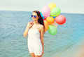Happy young woman with colorful balloons on beach near sea Royalty Free Stock Photo