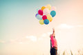 Happy young woman with colorful balloons, enjoy in the morning time at grassland Royalty Free Stock Photo