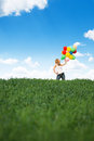 Happy young woman with colorful balloons on a green meadow Royalty Free Stock Image