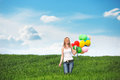 Happy young woman with colorful balloons on a green meadow Stock Images