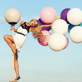 Happy young woman with colorful latex balloons girl big beauty romantic girl outdoors long wavy hair having fun on a lamppost Stock Images