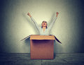 Happy young woman coming out from a small box Royalty Free Stock Photo