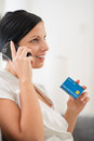 Happy young woman with credit card speaking mobile Stock Photography